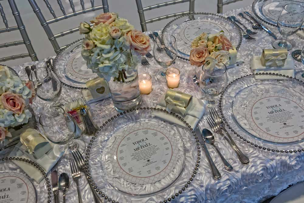 Gorgeous Textured White Linens, Silver Bamboo Chairs, and Silver-rimmed Plate Chargers Wedding Party Table setup
