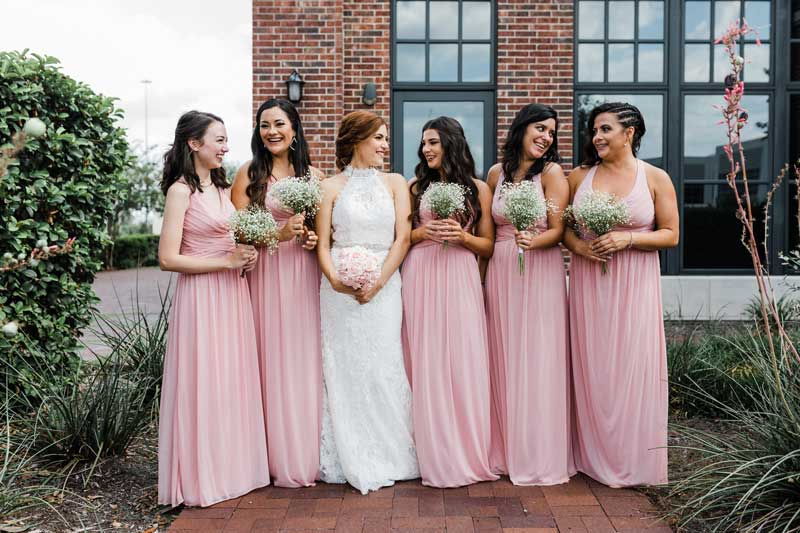 bride with bridesmaids outdoors at The Ark in Katy