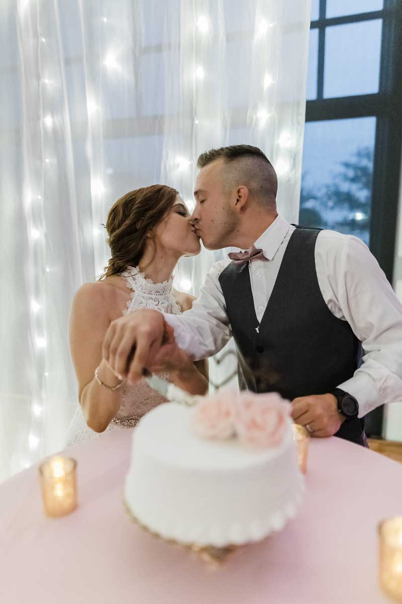 photo of bride and groom kissing while cutting cake