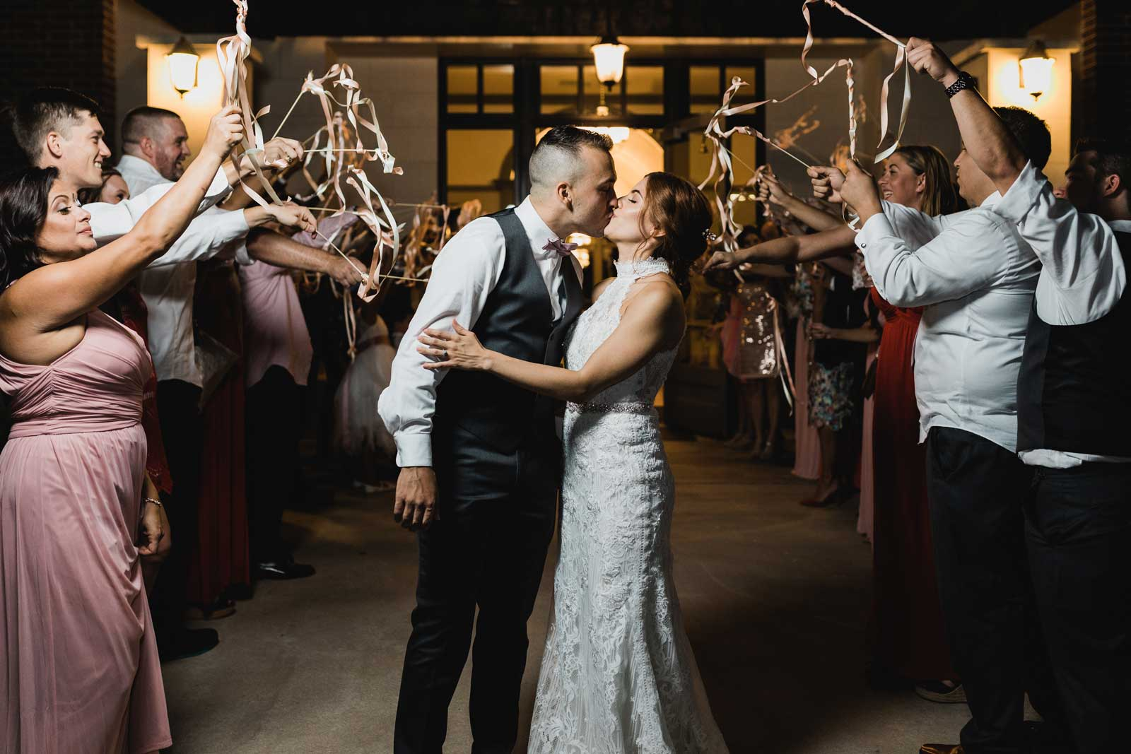 photo of bride and groom kissing while leaving the venue