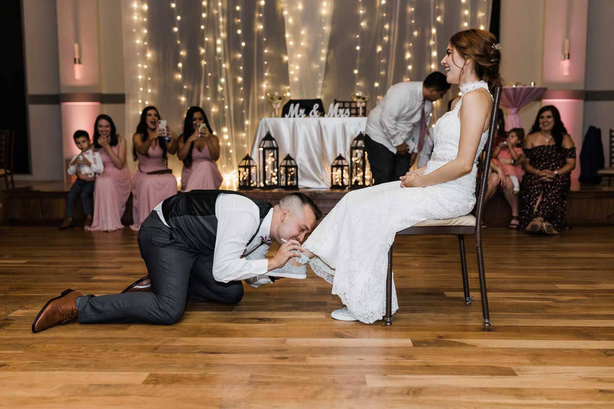 photo of the groom removing the bride's garter