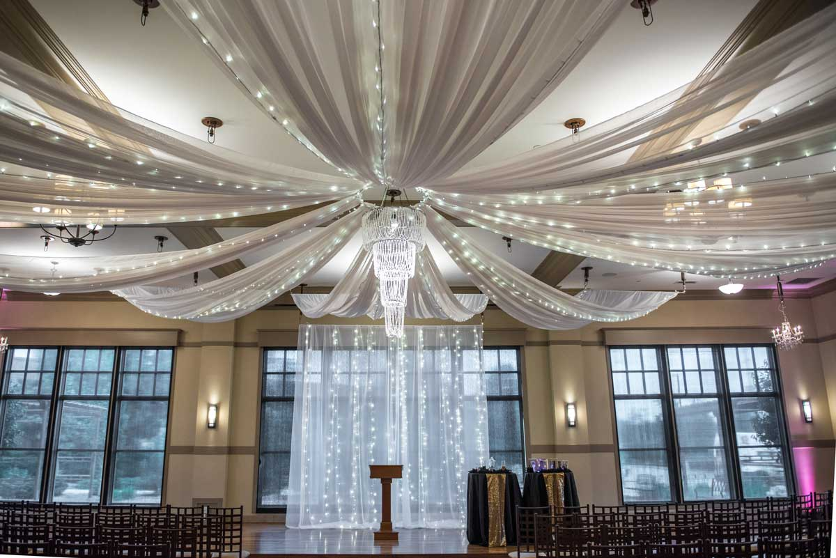 Sweeping fabric and lights chandelier over the setting for a wedding ceremony at The Ark in Katy